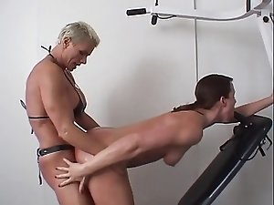Muscular dyke fucks submissive chick with strap on during work out